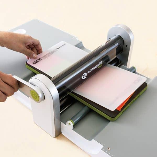 GO! Fabric Cutter Starter Set (AQ55100S) - GO! Fabric Cutter Shown with a fabric cutting die and cutting mat being rolled through the cutter.